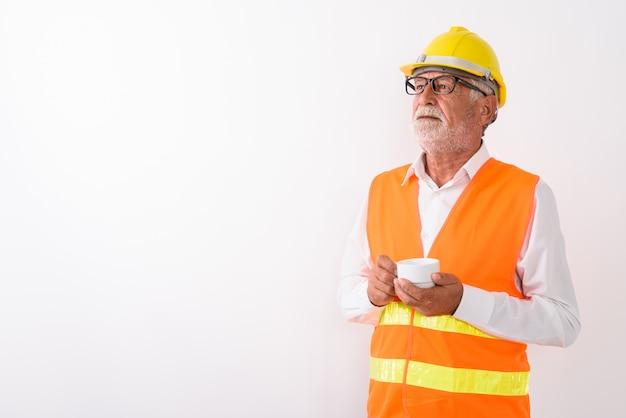 Hübscher älterer bärtiger mannbauarbeiter, der kaffeetasse denkt und hält, während brillen auf weiß tragen