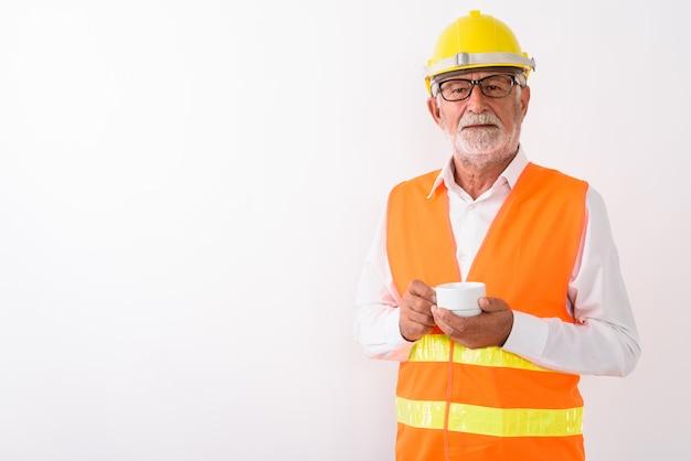 Hübscher älterer bärtiger mannbauarbeiter, der kaffeetasse hält, während brillen auf weiß tragen