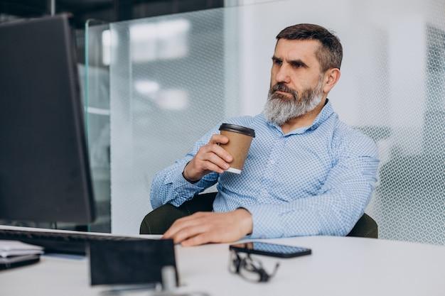 Hübscher älterer geschäftsmann, der im büro am computer arbeitet