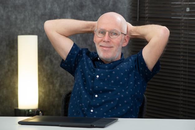 Hübscher älterer geschäftsmann, der im büro sich entspannt
