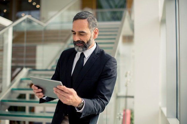 Hübscher älterer geschäftsmann mit digitaler tablette im modren büro