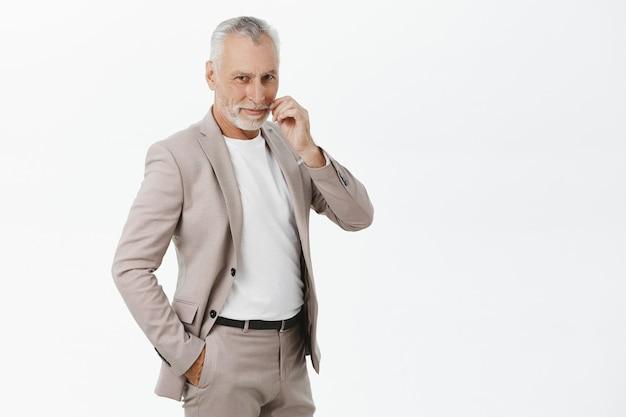 Hübscher älterer männlicher unternehmer im anzug, der erfreut schaut