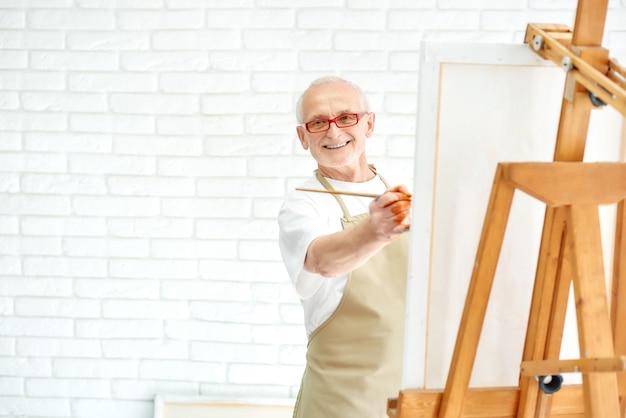 Hübscher älterer maler, der bunte malerei am hellen studio zeichnet.