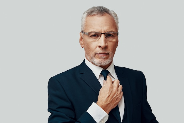 Hübscher älterer mann im vollen anzug, der in die kamera schaut und seine krawatte im stehen vor grauem hintergrund anpasst