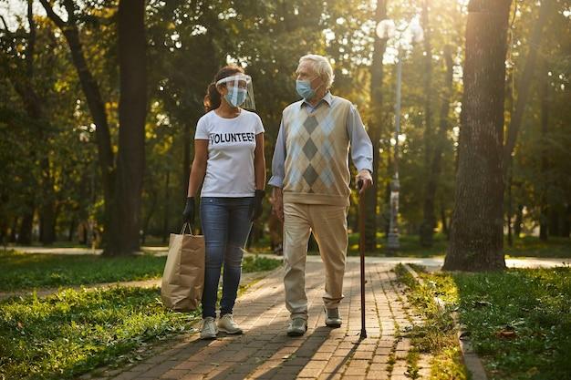 Hübscher älterer mann in freizeitkleidung, der zeit mit einer jungen schönen frau im freien verbringt