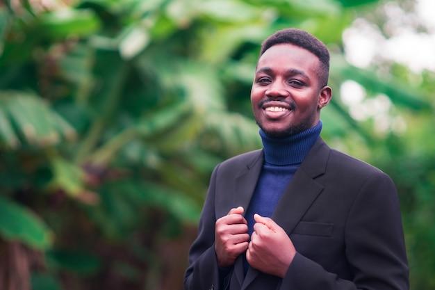 Hübscher afrikanischer geschäftsmann, der im trendigen formellen schwarzen anzug steht. mann mit bart trägt blauen langarm oder pullover