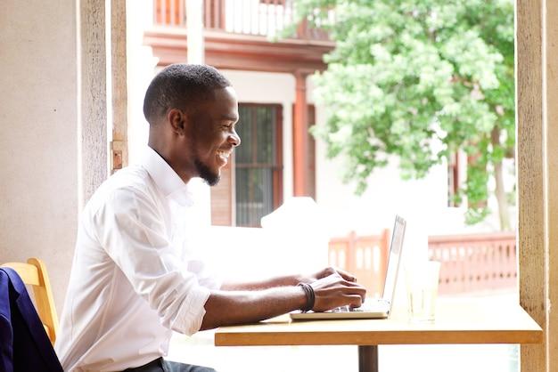 Hübscher afrikanischer geschäftsmann, der mit laptop lächelt