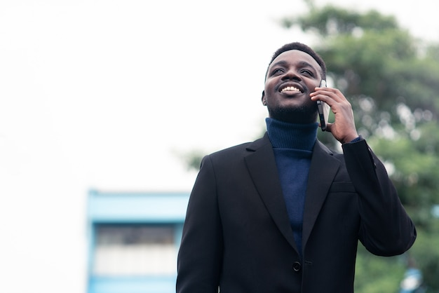 Hübscher afrikanischer geschäftsmann, der smartphone im trendigen formellen schwarzen anzug verwendet. mann mit bart trägt blauen langarm oder pullover