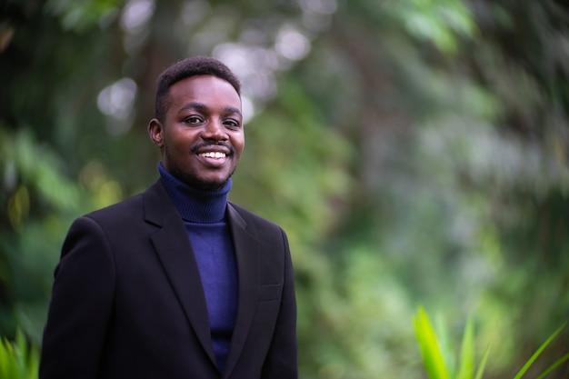 Hübscher afrikanischer geschäftsmann im trendigen formellen schwarzen anzug. mann mit bart trägt blauen langarm oder pullover