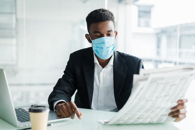 Hübscher afrikanischer geschäftsmann tragen in der medizinischen maske mit zeitung am morgen nahe geschäftszentrumbüro