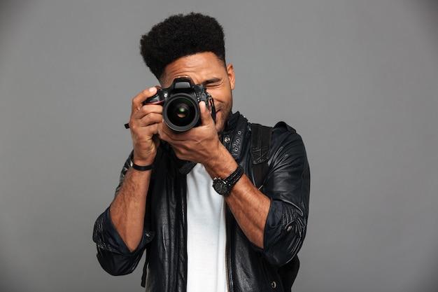 Hübscher afrikanischer kerl mit dem stilvollen haarschnitt, der foto auf digitalkamera macht