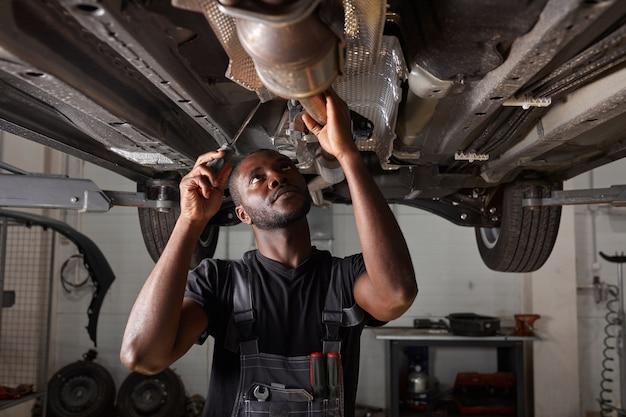 Hübscher afrikanischer mann, der boden des autos repariert