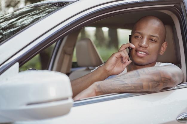 Hübscher afrikanischer mann, der das reisen mit dem auto auf einem roadtrip genießt