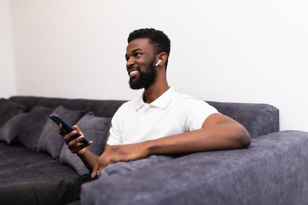 Hübscher afrikanischer mann, der einen anruf über airpods macht, während er auf einer couch in seinem wohnzimmer sitzt