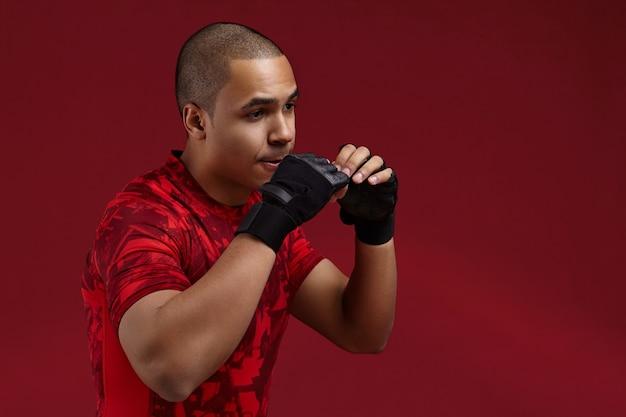 Hübscher afrikanischer mann, der fingerlose schwarze lederhandschuhe trägt, die im fitnessstudio trainieren, an der schlagtechnik arbeiten, sich müde und erschöpft fühlen. junger dunkelhäutiger kämpfer mit starken armen, die im studio boxen