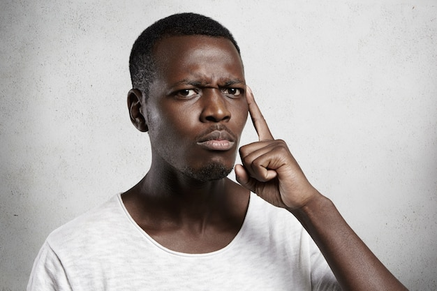 Hübscher afrikanischer mann mit misstrauen und zweifel, der gegen betonwand aufwirft.