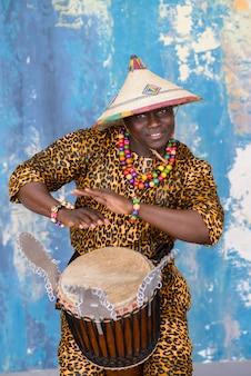 Hübscher afrikanischer schlagzeuger, der in traditioneller tracht getragen wird, die auf djembe-trommel spielt
