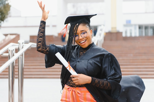 Hübscher afrikanischer student in der abschlusskappe und im kleid vor dem schulgebäude