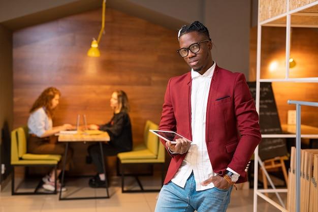 Hübscher afrikanischer student oder zeitgenössischer geschäftsmann mit touchpad-vernetzung im café mit zwei mädchen, die laptops verwenden