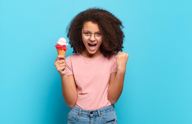 Hübscher afro-teenager, der aggressiv mit einem wütenden ausdruck oder mit geballten fäusten schreit, um erfolg zu feiern. sumer-eis-konzept