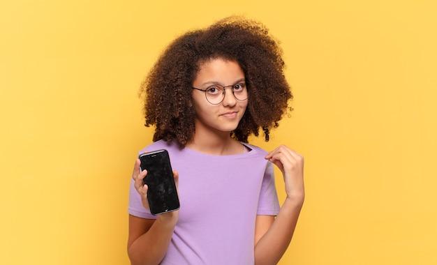 Hübscher afro-teenager, der arrogant, erfolgreich, positiv und stolz aussieht, auf sich selbst zeigt und eine zelle hält