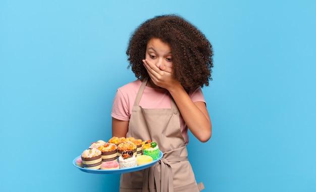 Hübscher afro-teenager, der den mund mit den händen mit einem schockierten, überraschten ausdruck bedeckt, ein geheimnis bewahrt oder hoppla sagt. humorvolles bäcker-konzept