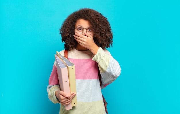 Hübscher afro-teenager, der den mund mit den händen mit einem schockierten, überraschten ausdruck bedeckt, ein geheimnis hält oder oops sagt. studentisches konzept