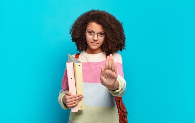 Hübscher afro-teenager, der ernst, streng, unzufrieden und wütend aussieht und eine offene handfläche zeigt, die eine stoppgeste macht