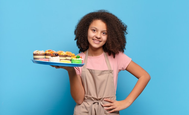 Hübscher afro-teenager, der glücklich mit einer hand auf hüfte und selbstbewusster, positiver, stolzer und freundlicher haltung lächelt. humorvolles bäckerkonzept