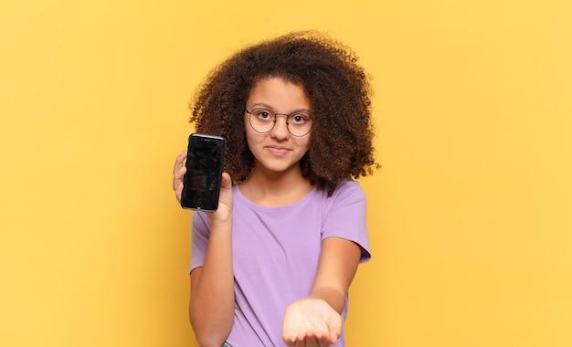 Hübscher afro-teenager, der glücklich mit freundlichem, selbstbewusstem, positivem blick lächelt, ein objekt oder konzept anbietet und zeigt und eine zelle hält