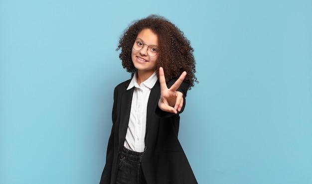 Hübscher afro-teenager, der glücklich, sorglos und positiv lächelt und aussieht und mit einer hand sieg oder frieden gestikuliert. humorvolles geschäftskonzept