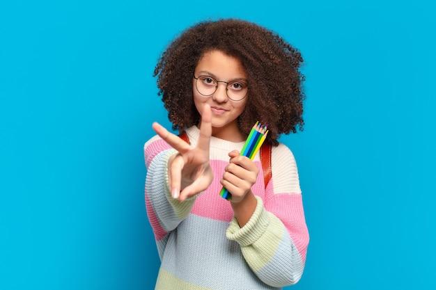 Hübscher afro-teenager, der glücklich, sorglos und positiv lächelt und aussieht und mit einer hand sieg oder frieden gestikuliert. studentisches konzept