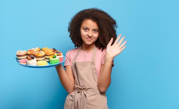 Hübscher afro-teenager, der glücklich und fröhlich lächelt, die hand winkt, sie begrüßt und begrüßt oder sich verabschiedet. humorvolles bäckerkonzept