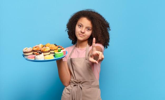 Hübscher afro-teenager, der lächelt und freundlich aussieht, nummer eins oder zuerst mit der hand nach vorne zeigt und herunterzählt. humorvolles bäcker-konzept