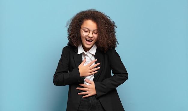 Hübscher afro-teenager, der laut über einen lustigen witz lacht, sich glücklich und fröhlich fühlt und spaß hat. humorvolles geschäftskonzept