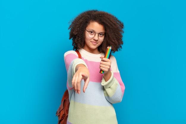 Hübscher afro-teenager, der mit einem zufriedenen, selbstbewussten, freundlichen lächeln nach vorne zeigt und sich für sie entscheidet. studentisches konzept