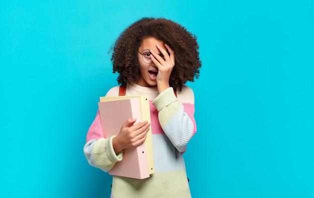 Hübscher afro-teenager, der schockiert, verängstigt oder verängstigt aussieht, das gesicht mit der hand bedeckt und zwischen den fingern späht. studentenkonzept