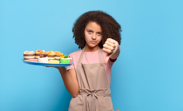 Hübscher afro-teenager, der sich böse, wütend, verärgert, enttäuscht oder unzufrieden fühlt und mit einem ernsten blick die daumen nach unten zeigt. humorvolles bäcker-konzept