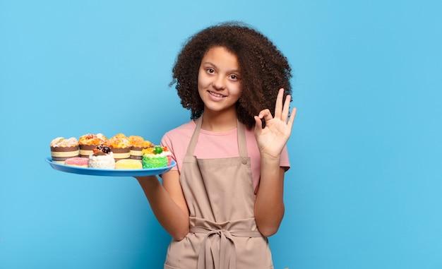 Hübscher afro-teenager, der sich glücklich, entspannt und zufrieden fühlt, zustimmung mit einer guten geste zeigt und lächelt. humorvolles bäcker-konzept