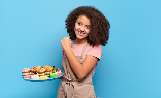 Hübscher afro-teenager, der sich glücklich, positiv und erfolgreich fühlt, motiviert, wenn er sich einer herausforderung stellt oder gute ergebnisse feiert. humorvolles bäcker-konzept