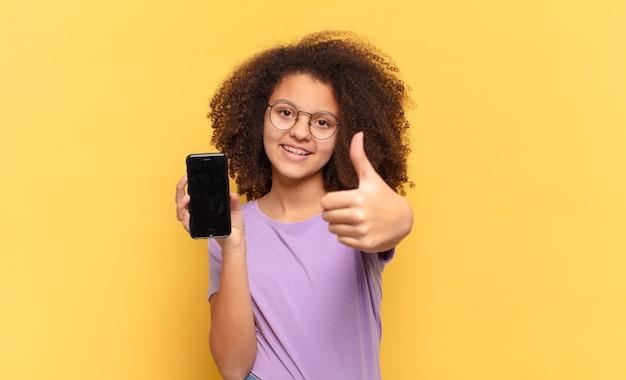 Hübscher afro-teenager, der sich stolz, sorglos, selbstbewusst und glücklich fühlt, positiv mit daumen nach oben lächelt und eine zelle hält