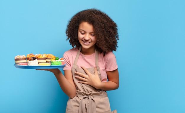 Hübscher afro-teenager, der über einen lustigen witz laut lacht, sich glücklich und fröhlich fühlt und spaß hat. humorvolles bäcker-konzept
