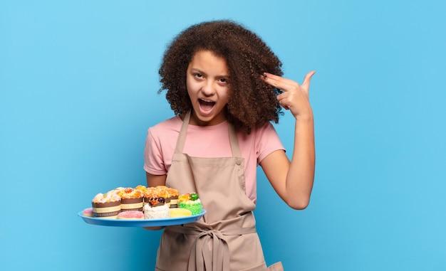 Hübscher afro-teenager, der unglücklich und gestresst aussieht, selbstmordgeste, die waffenzeichen mit der hand macht und auf den kopf zeigt. humorvolles bäckerkonzept