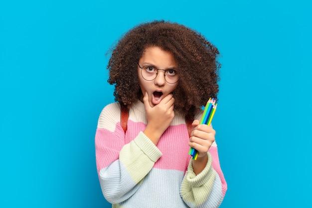 Hübscher afro-teenager mit weit geöffnetem mund und augen und hand am kinn