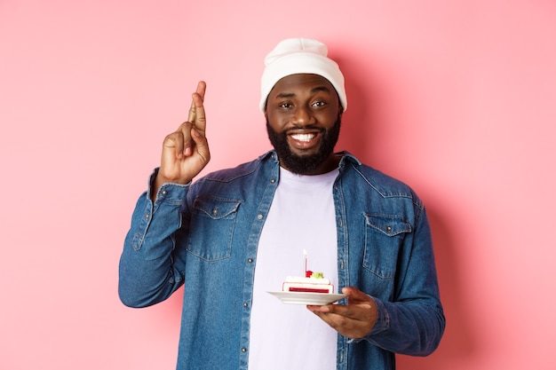 Hübscher afroamerikaner, der geburtstag feiert, wünsche mit gekreuzten fingern wünscht, geburtstagskuchen mit kerze hält und vor rosa hintergrund steht
