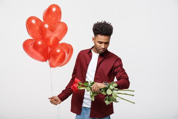 Hübscher afroamerikaner, der herzballon hält und zeit auf seiner uhr überprüft.