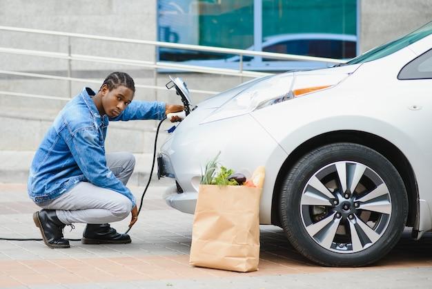 Hübscher afroamerikaner, der nahe seinem neuen modernen elektroauto sitzt und stecker des ladegeräts hält
