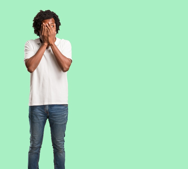 Hübscher afroamerikaner fühlt sich besorgt und erschrocken, gesicht, konzept der furcht und angst schauend und bedeckend