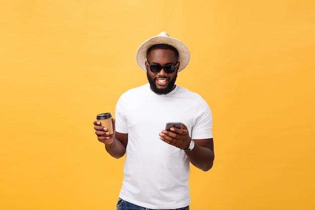 Hübscher afroamerikaner mit handy und nehmen kaffeetasse weg.