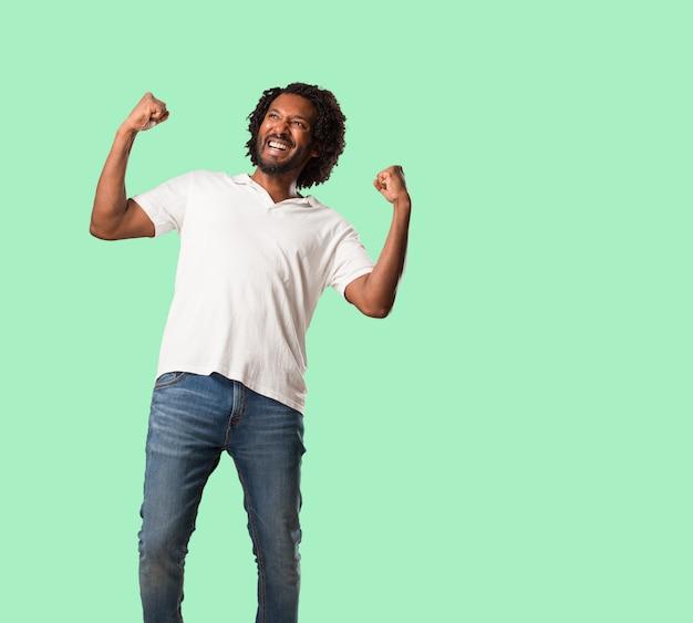 Hübscher afroamerikaner sehr glücklich und aufgeregt, arme anheben, einen sieg oder einen erfolg feiern und die lotterie gewinnen